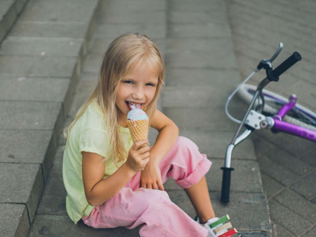 cute child with ice cream sitting on city steps near bicycle alo