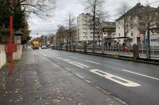 Busspur auf der Aachener Straße mit dem Schriftzug Bus auf dem Asphalt und einer Straßenbahnhaltestelle in der rechten Bildhälfte